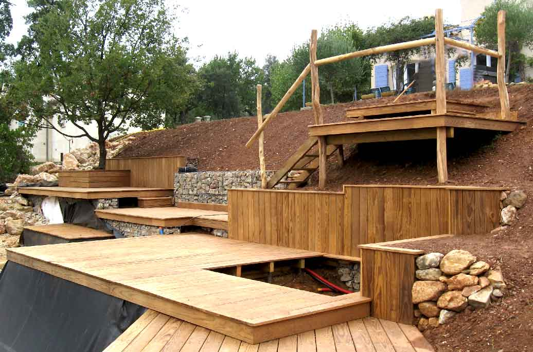 Succession de terrasses, marches et escalier en bois associé à la pierre