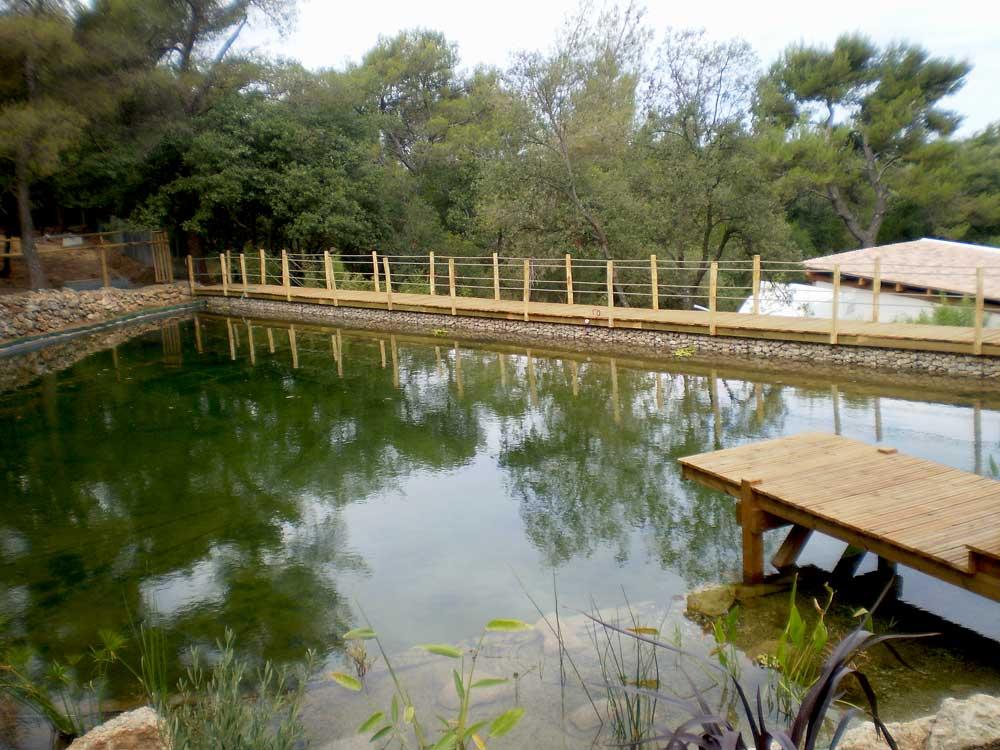 Bassin de rétention d'eau soutenue par un mur de gabions et passerelle bois